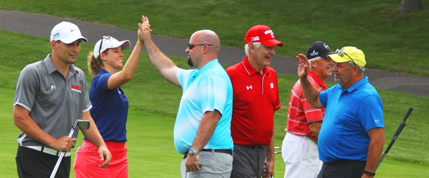 Andy North with a group of golfers, hi-fiving after a good shot.