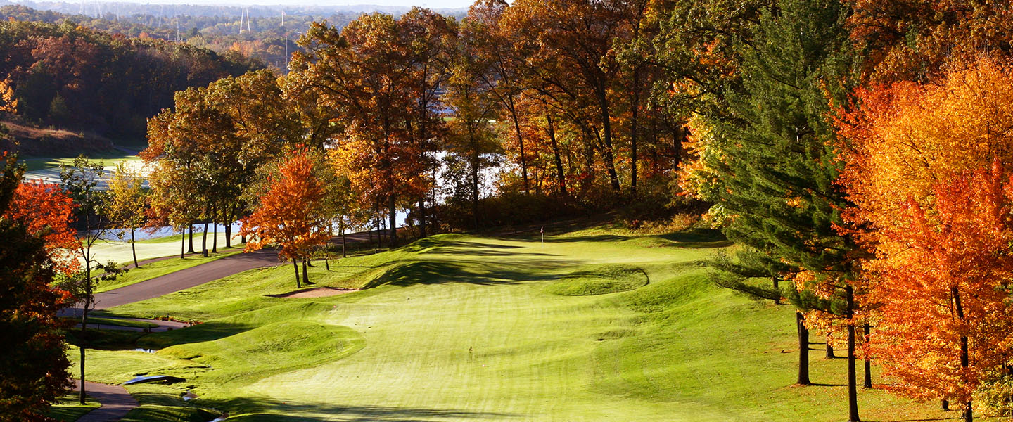 Fairway surrounded by trees in fall colors.