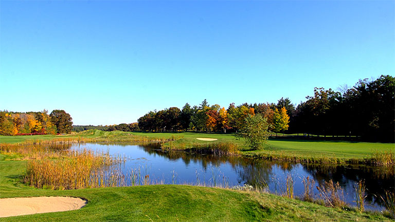 The fairway lined by trees in fall color and a water feature