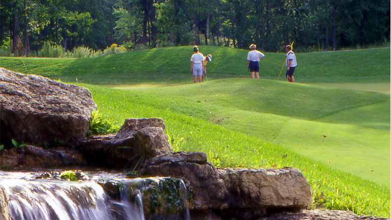 A group of women golfers with a waterfall in the foreground