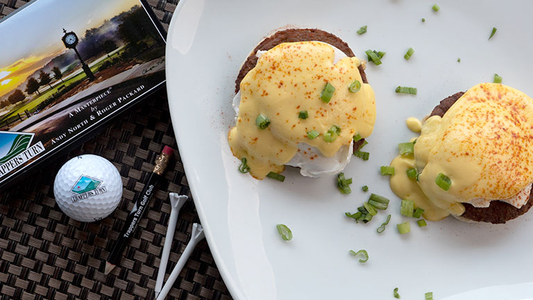 Eggs Benedict garnished with scallion