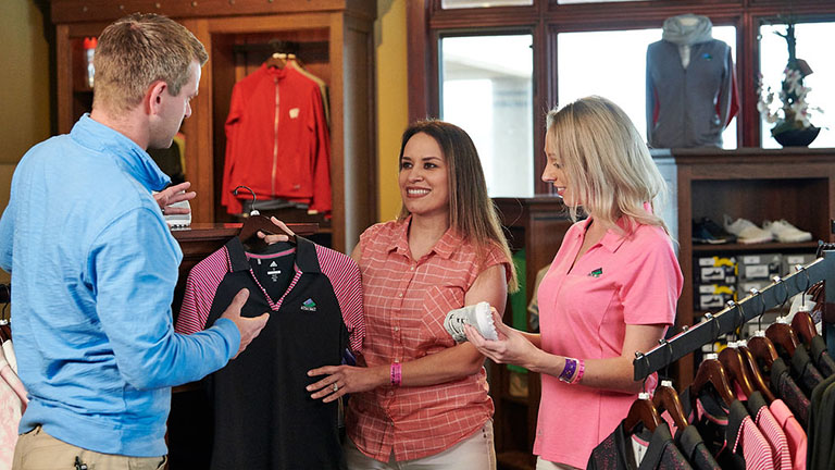 Trappers Turn golf shop staff assists two shoppers in choosing a golf shirt