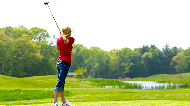 Woman golfer taking a driving shot over Mystic Lake